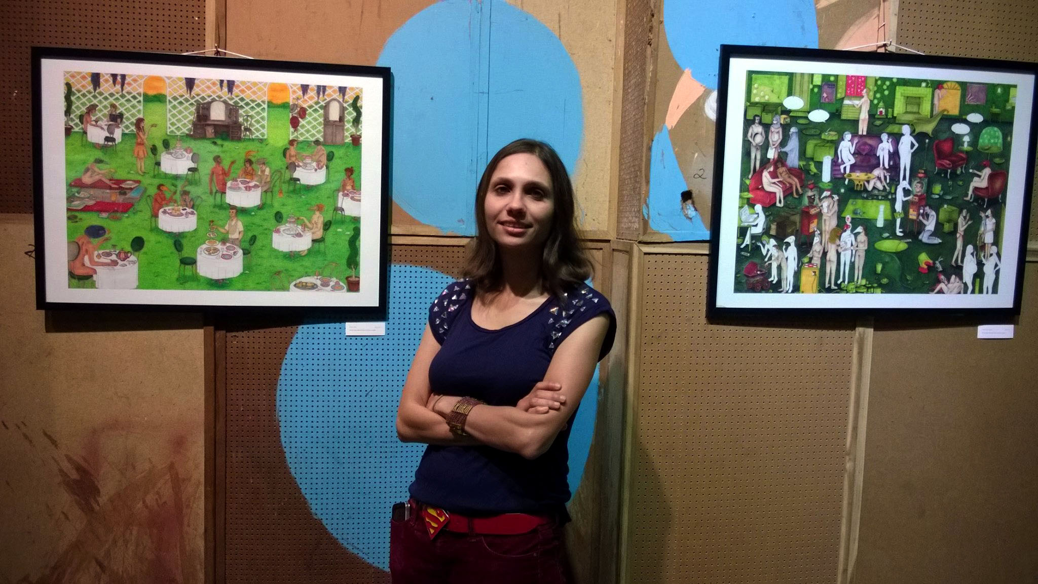 Photo of Janine Shroff in front of 2 paintings by Nikhil Hemranjani at Sitara Studios